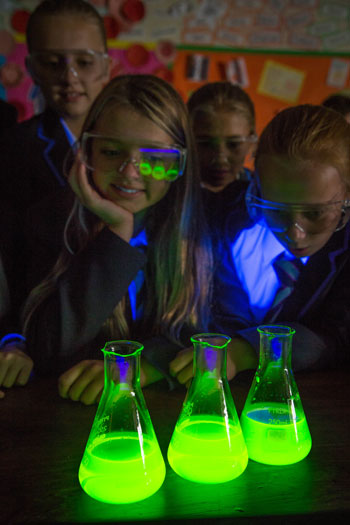 Pupils in science class watching illuminous chemicals